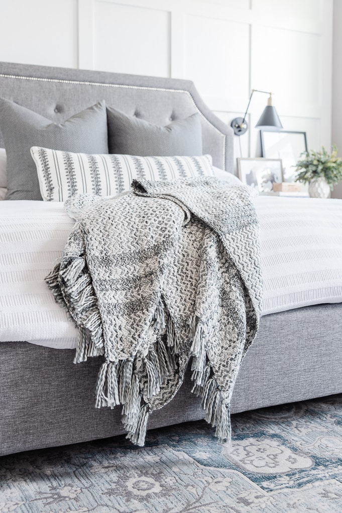 gray pattern throw blanket on a white bed