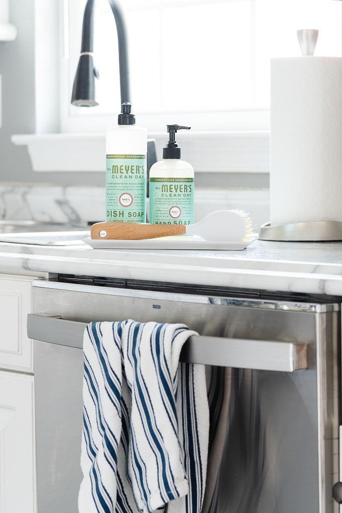 mrs. meyers basil scent hand soap and dish soap in a tray on kitchen countertop