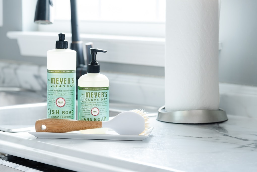 mrs. meyers basil scent hand soap and dish soap in kitchen with sponge on a tray