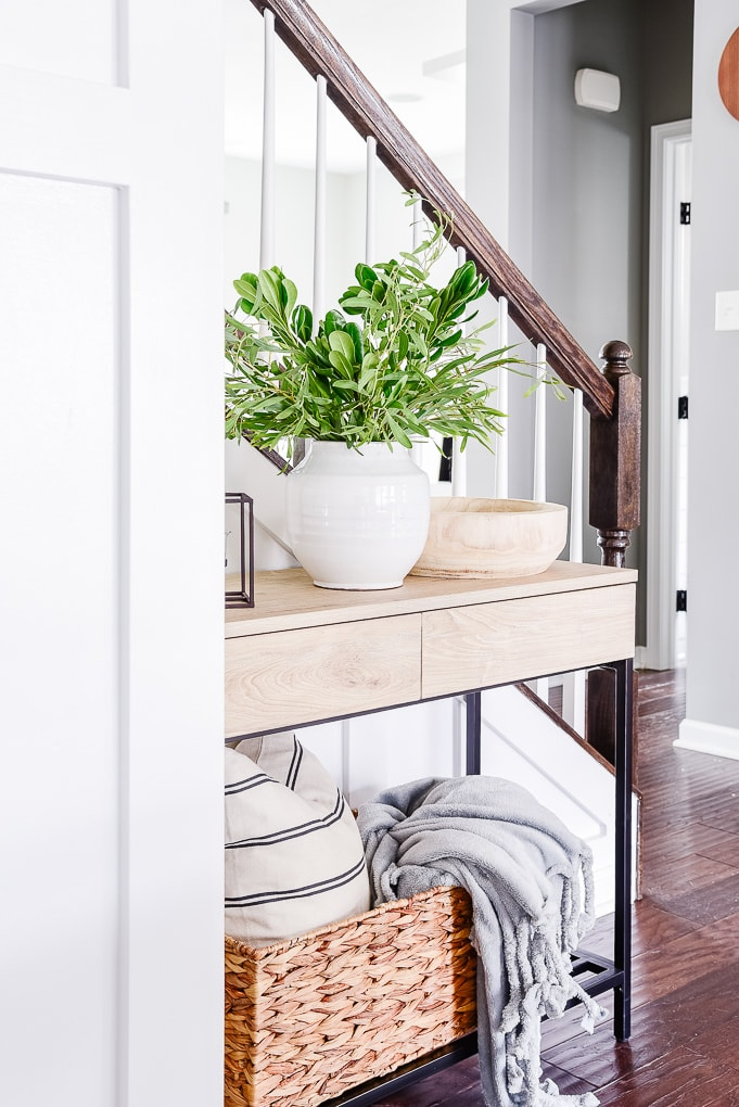 natural wood console table with white vase and greenery and decor on the bottom shelf