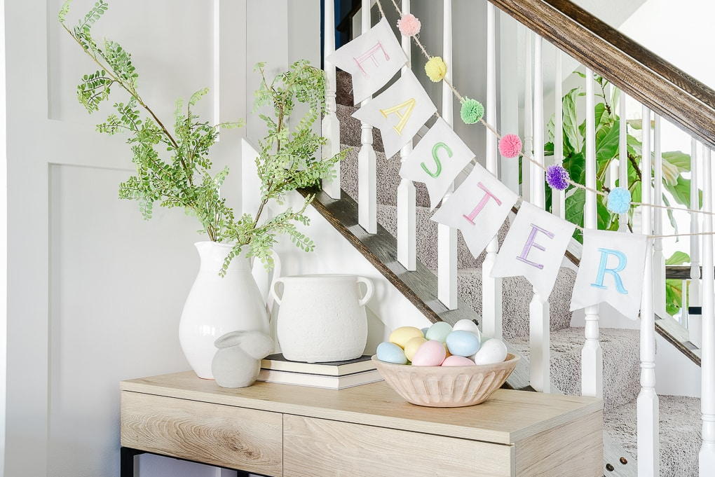 console table next to staircase decorated for Easter with white vases colorful Easter eggs and a fabric Easter banner
