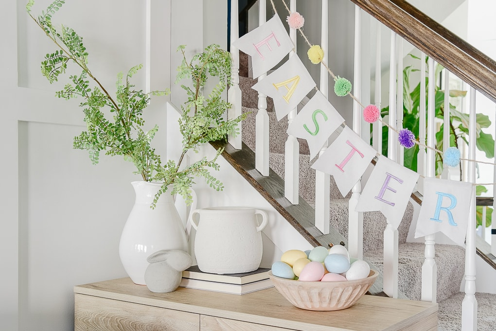 console table decorated for Easter with white and pastel colors