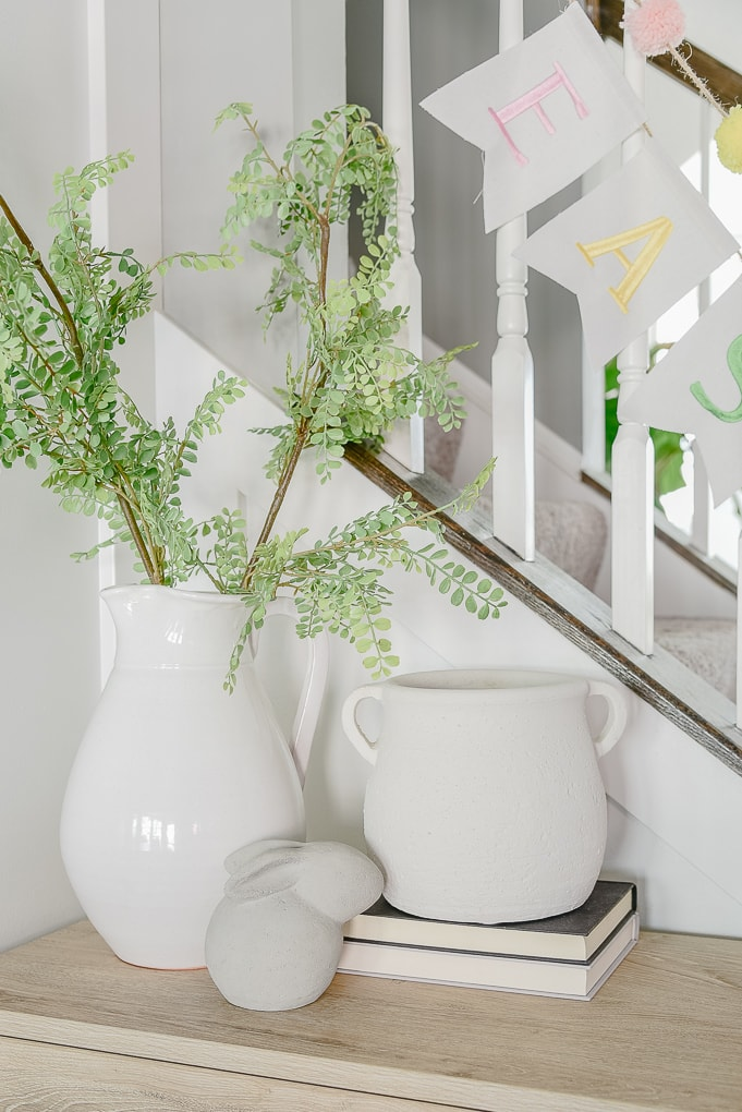 white pitcher vase and white stoneware vase on console table decorated for spring and Easter