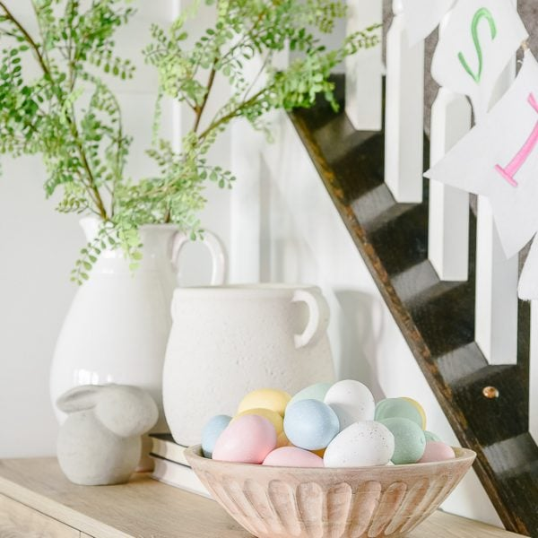 natural wooden bowl filled with eggs on console table and white vases in the background