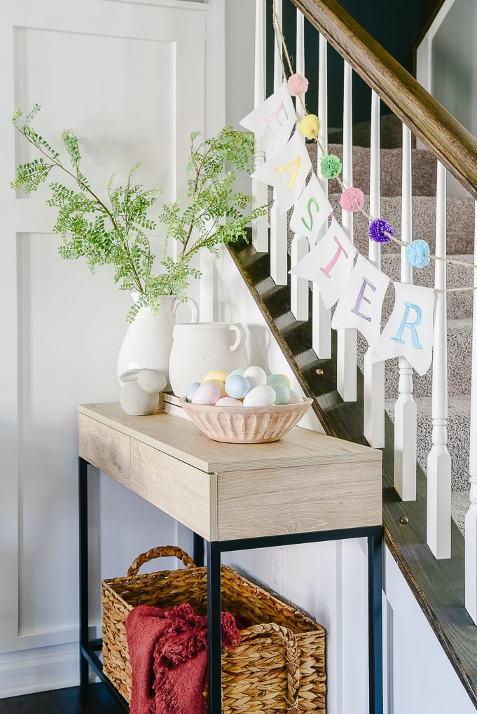 natural wood console table decorated for easter with spring home decor
