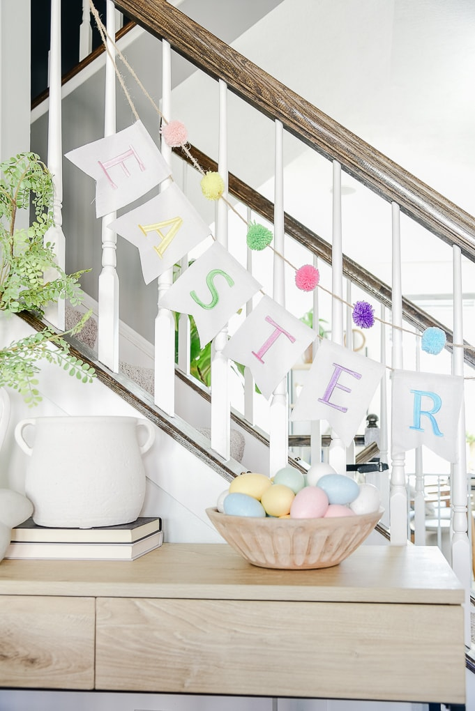 Easter fabric banner hanging from staircase railing above console table