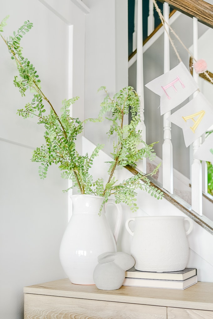 white vases on console table decorated for spring with cement bunny decorative object in front