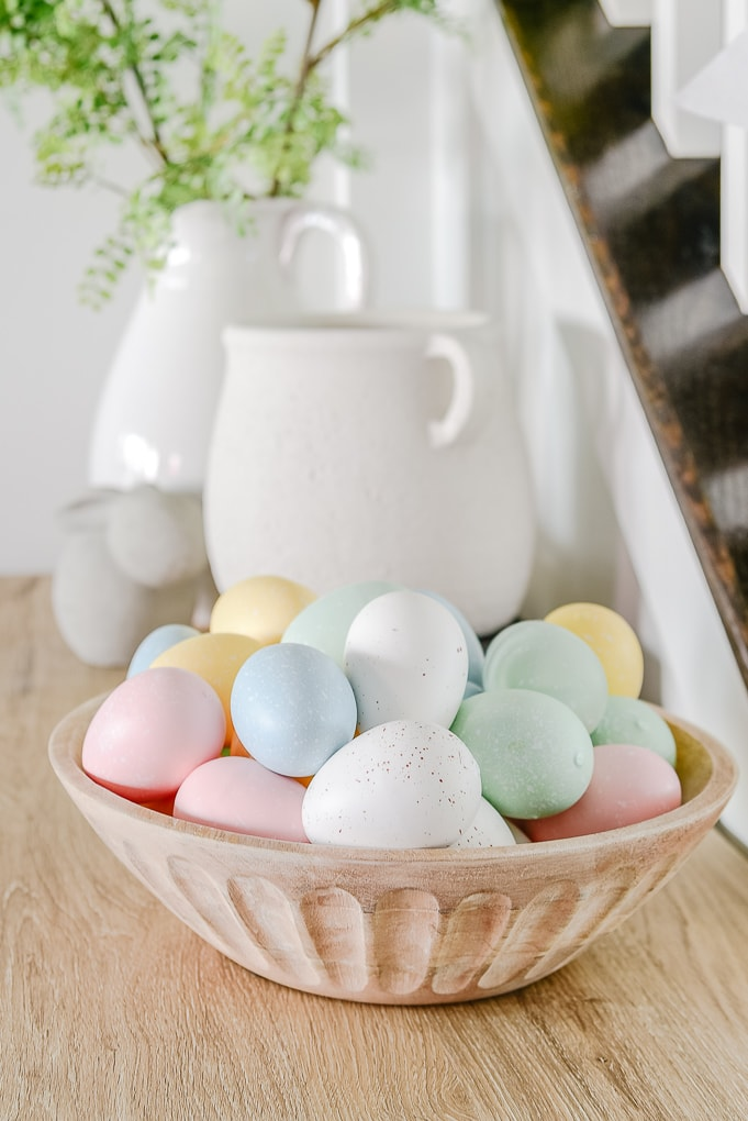 wooden bowl filled with pastel decorative Easter eggs