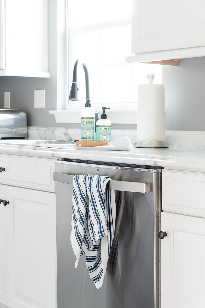 clean kitchen sink with towel on dishwasher and Mrs. Meyers cleaning products on the counter