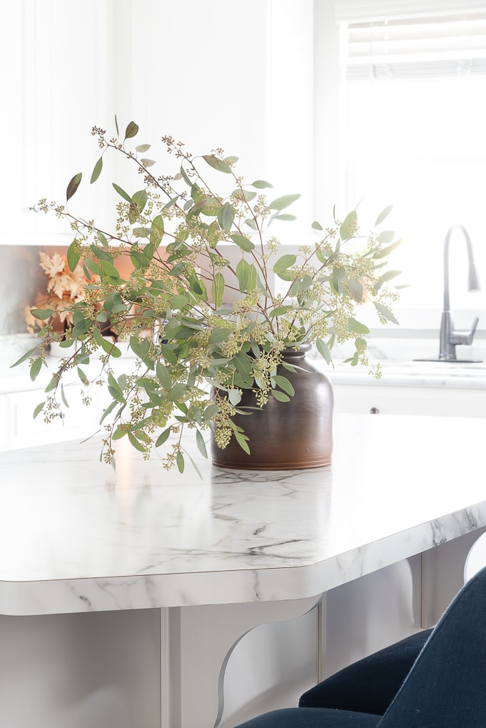 fresh greenery in brown vintage vase in white kitchen on clear cleaned countertops