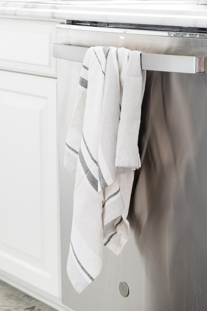kitchen towel hanging on handle of stainless steel dishwasher