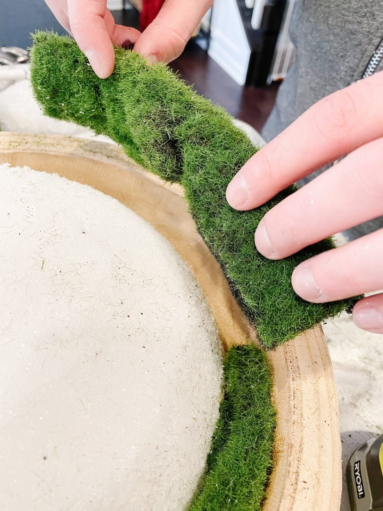 folded faux moss sheets being attached to wooden bowl