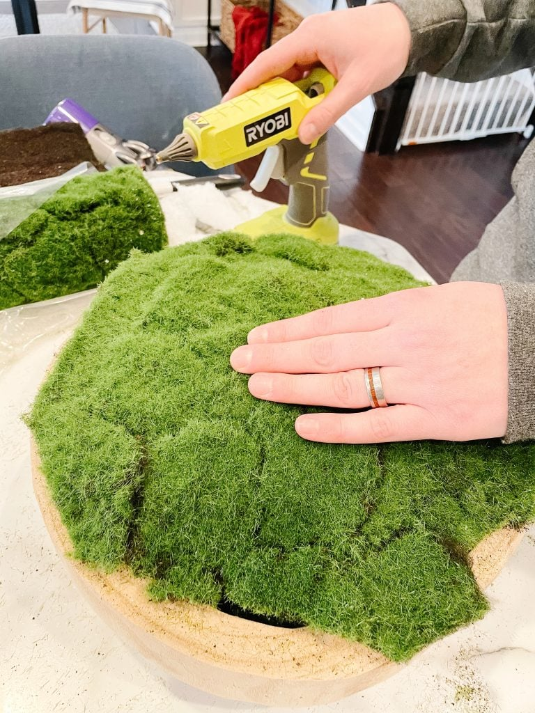 using hot glue to attach faux moss sheet to wooden bowl