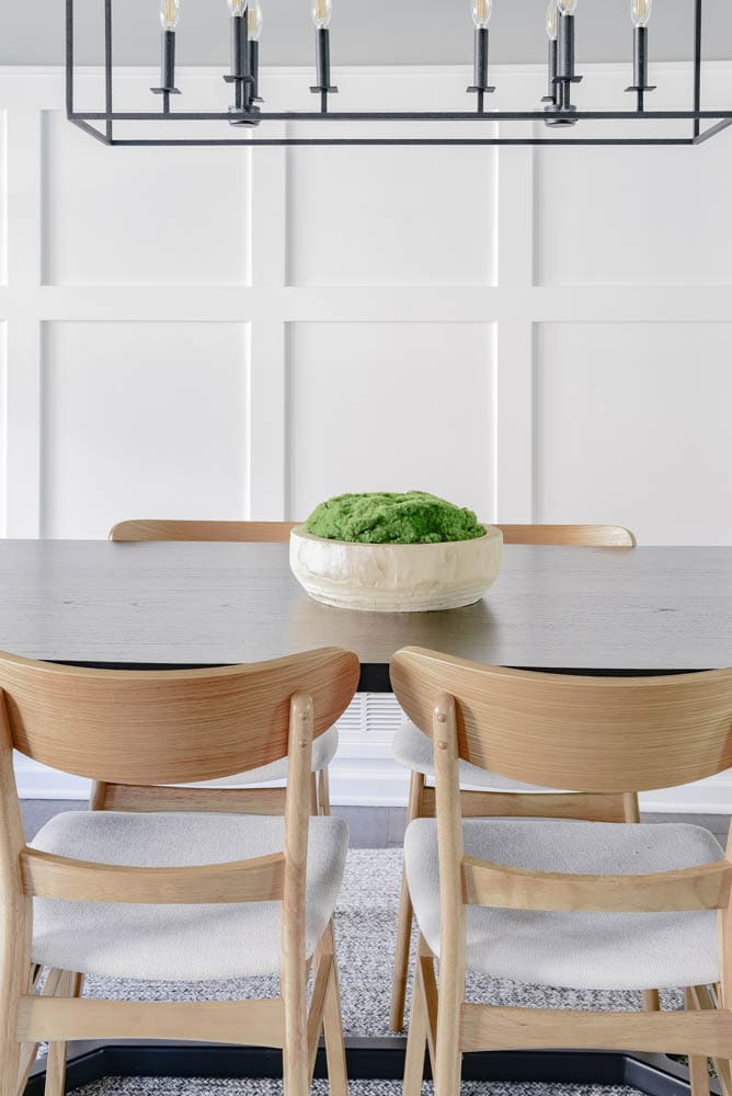 wooden bowl moss centerpiece on black dining room table